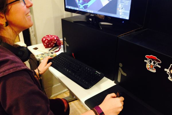 Mari sitting at her computer, illustrating game art